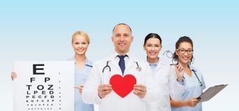 Группа в составе усмехаясь доктора с красной формой сердца Стоковая Фотография