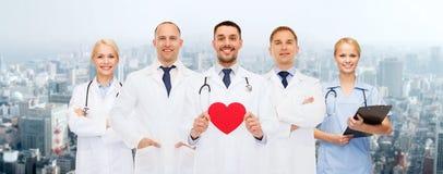 Группа в составе усмехаясь доктора с красной формой сердца Стоковое фото RF