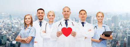 Группа в составе усмехаясь доктора с красной формой сердца Стоковые Изображения