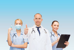Группа в составе усмехаясь доктора с показывать большие пальцы руки вверх Стоковая Фотография RF