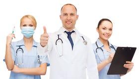 Группа в составе усмехаясь доктора с показывать большие пальцы руки вверх Стоковая Фотография