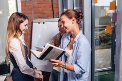 Группа в составе усмехаясь подруги смеясь над пока изучающ и пересматривающ для экзамена в библиотеке Стоковое Изображение