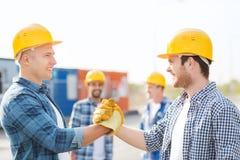 Группа в составе усмехаясь построители в защитных шлемах outdoors Стоковая Фотография