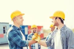 Группа в составе усмехаясь построители в защитных шлемах outdoors Стоковые Фотографии RF