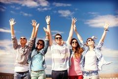 Группа в составе усмехаясь подростки держа руки вверх Стоковые Фотографии RF