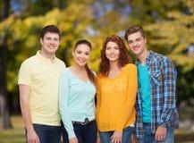 Группа в составе усмехаясь подростки над зеленым парком Стоковое Фото