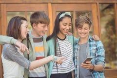 Группа в составе усмехаясь подруги по школе используя мобильный телефон Стоковая Фотография RF