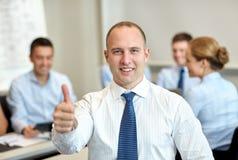 Группа в составе усмехаясь предприниматели встречая в офисе Стоковое Изображение