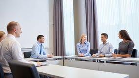 Группа в составе усмехаясь предприниматели встречая в офисе Стоковая Фотография