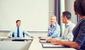 Группа в составе усмехаясь предприниматели встречая в офисе Стоковое Фото