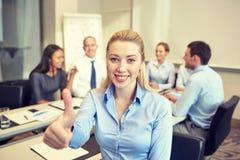 Группа в составе усмехаясь предприниматели встречая в офисе Стоковые Изображения