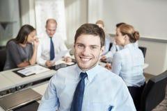 Группа в составе усмехаясь предприниматели встречая в офисе Стоковые Изображения RF