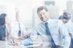 Группа в составе усмехаясь предприниматели встречая в офисе Стоковое Изображение RF
