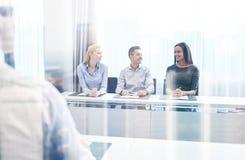 Группа в составе усмехаясь предприниматели встречая в офисе Стоковое фото RF