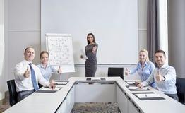 Группа в составе усмехаясь предприниматели показывая большие пальцы руки вверх стоковая фотография
