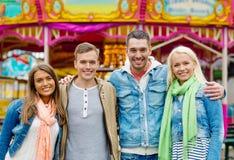 Группа в составе усмехаясь друзья в парке атракционов Стоковые Фотографии RF