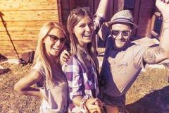 Группа в составе усмехаясь друзья принимая смешное selfie с умным телефоном Стоковое фото RF