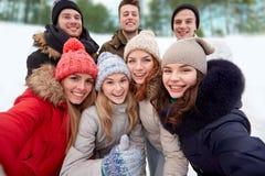 Группа в составе усмехаясь друзья принимая selfie outdoors Стоковая Фотография RF
