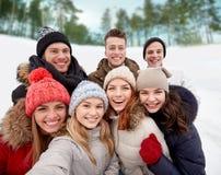 Группа в составе усмехаясь друзья принимая selfie outdoors Стоковые Фотографии RF