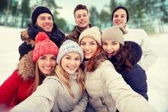 Группа в составе усмехаясь друзья принимая selfie outdoors Стоковое фото RF