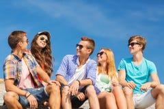 Группа в составе усмехаясь друзья сидя на улице города Стоковое Изображение RF