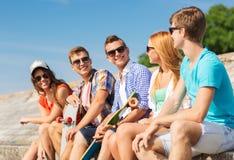 Группа в составе усмехаясь друзья сидя на улице города Стоковое Изображение