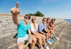 Группа в составе усмехаясь друзья сидя на улице города Стоковое фото RF
