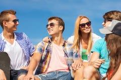 Группа в составе усмехаясь друзья сидя на улице города Стоковое Фото