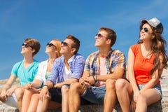 Группа в составе усмехаясь друзья сидя на улице города Стоковые Изображения RF
