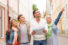 Группа в составе усмехаясь друзья с городом карты исследуя Стоковые Изображения RF