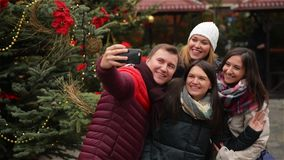 Группа в составе усмехаясь человек и женщины принимая Selfie Outdoors около дерева Xmas Друзья имея потеху на рождественской ярма сток-видео