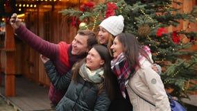 Группа в составе усмехаясь человек и женщины принимая Selfie Outdoors около дерева Xmas Друзья имея потеху на рождественской ярма видеоматериал