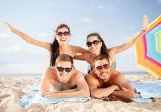 Группа в составе усмехаясь люди имея потеху на пляже Стоковые Изображения