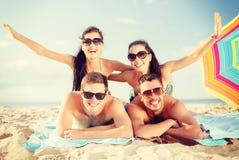 Группа в составе усмехаясь люди имея потеху на пляже Стоковое Фото