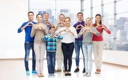 Группа в составе усмехаясь люди показывая руку сердца подписывает Стоковые Изображения