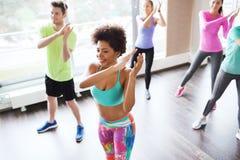 Группа в составе усмехаясь люди танцуя в спортзале или студии Стоковые Изображения