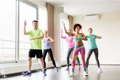 Группа в составе усмехаясь люди танцуя в спортзале или студии Стоковые Фото