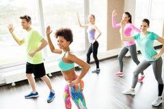Группа в составе усмехаясь люди танцуя в спортзале или студии Стоковые Фотографии RF