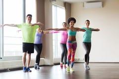 Группа в составе усмехаясь люди танцуя в спортзале или студии Стоковое Фото