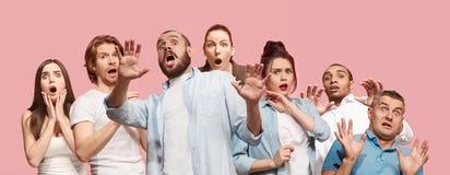 Группа в составе устрашенные руки людей, женщины и человека напряжённые держа на голове, ужаснутой в панике, крича стоковое изображение rf