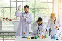 Группа в составе ученый работая кладя медицинский образец химикатов в пробирку на лаборатории совместно стоковая фотография rf