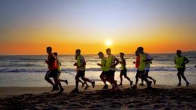 Группа в составе футболисты бежать на пляже на восходе солнца стоковая фотография