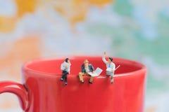 Группа в составе человек дела миниатюрный сидя на красном крае w кофейной чашки Стоковая Фотография