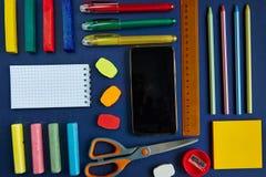 группа в составе школьные принадлежности на голубой предпосылке стоковая фотография