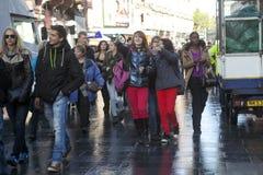 Группа в составе школьники идет на Ковент Гарден после дождя Девушки в красных брюках говоря друг к другу Стоковая Фотография