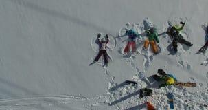 Группа в составе лыжники и snowboarders лежит в снеге Видео снято к трутню акции видеоматериалы