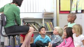 Группа в составе элементарные школьники времени уча прочитать видеоматериал