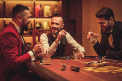 Группа в составе люди высшего класса играя покер в клубе ` s джентльмена Стоковое Изображение RF