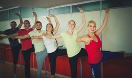 Группа в составе люди и женщины практикуя на barre балета стоковое изображение