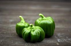 Группа в составе яркий красочный зеленый перец на черной деревенской предпосылке стоковое фото